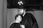80-414; Graduate Hugs President Earl Lazerson at Commencement